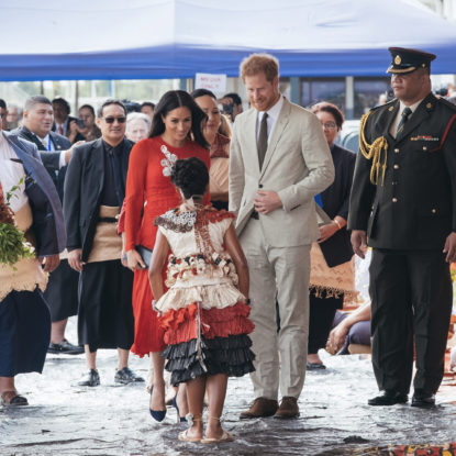 In this photo, the Duke and Duchess arrive in Tonga during their Pacific tour in 2018. A young local girl gifts the Duchess with a bouquet of flowers while the welcoming entourage gather behind for this official welcome to this island nation
