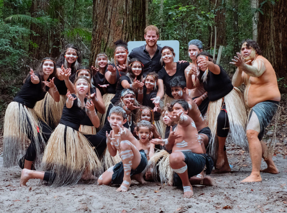 The Duke of Sussex poses for a group photo with members of the Aboriginal community on Fraser island, who live as one wit the forest. In this photo, they all smile as the locals are adorned with grass skirts and local attire