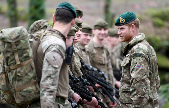In the South of England, The Duke of Sussex awards Green Berets to young troops who had just finished basic training. In this photo he smiles as he chats with one of the soldiers after their thirty mile loaded march