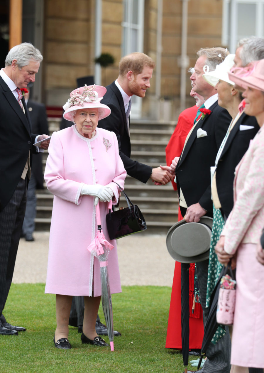 Queen Elizabeth II and the Duke of Sussex meet guests during a Royal Garden Party at Buckingham Palace in London. Her Majesty smiles at the camera as The Duke smiles and greets guests lined up to meet members of the Royal Family